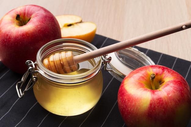 Jüdischer feiertag rosh hashanah mit honig und äpfeln auf holztisch.