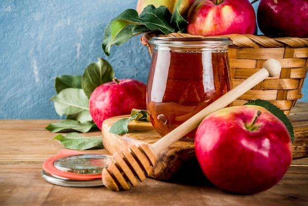 Jüdischer feiertag rosh hashanah oder apfelfest-tageskonzept, mit roten äpfeln, apfelblättern und honig im glas
