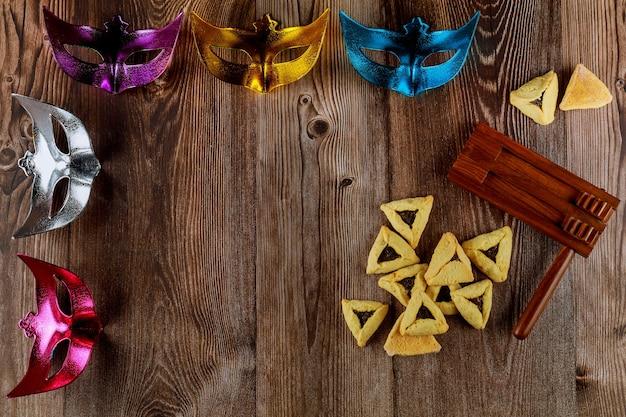 Jüdischer feiertagshintergrund mit hamantaschenplätzchen und karnevalsmaske für purim. speicherplatz kopieren.