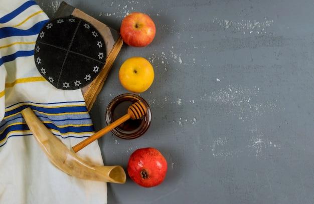 Jüdischer feiertagshonig und -äpfel mit granatapfel torah buch, kippah ein yamolka-talit