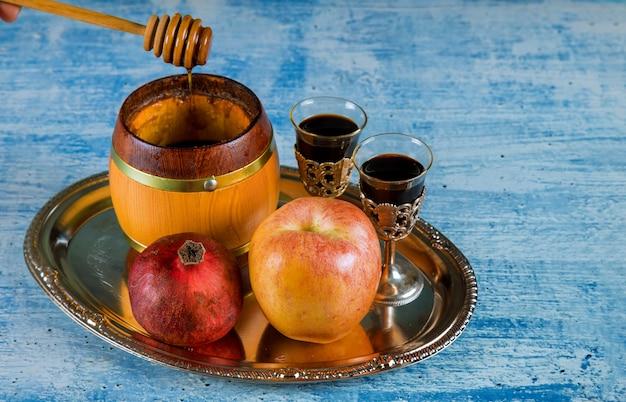 Jüdischer feiertagshonig und -äpfel mit granatapfel