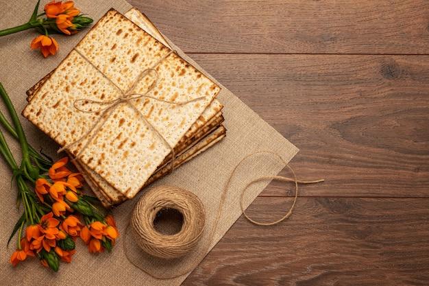 Jüdischer feiertagspessachhintergrund mit matze, blumen auf holztisch. von oben betrachten
