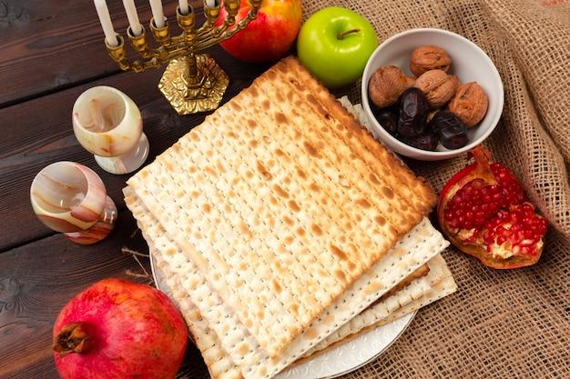 Jüdisches feiertag passahfest-fahnendesign mit wein, matzo auf hölzernem hintergrund.