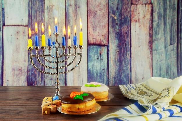 Jüdisches feiertagsbild des jüdischen feiertags-chanukka-hintergrundes mit traditionellem kandelaber der menorah und b...