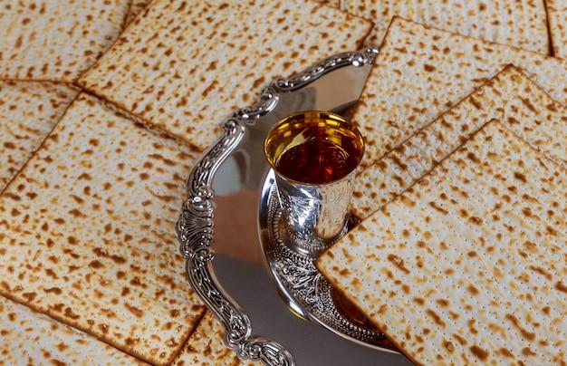 Jüdisches feiertagsbrot des passahfestmatzoh, koscherer wein der gläser über holztisch.