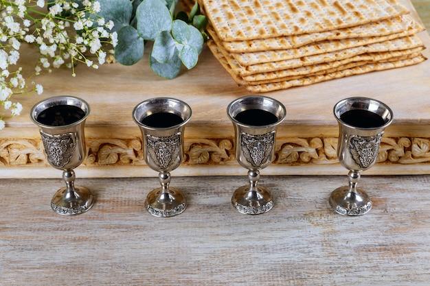 Jüdisches feiertagsbrot des passahfestmatzoh, koscherer wein mit vier gläsern über holztisch.