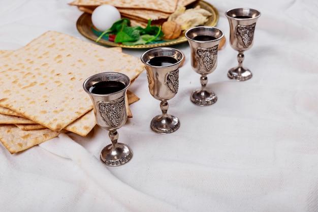 Jüdisches feiertagsbrot des passahfestmatzoh, vier gläser reiner wein über holztisch.