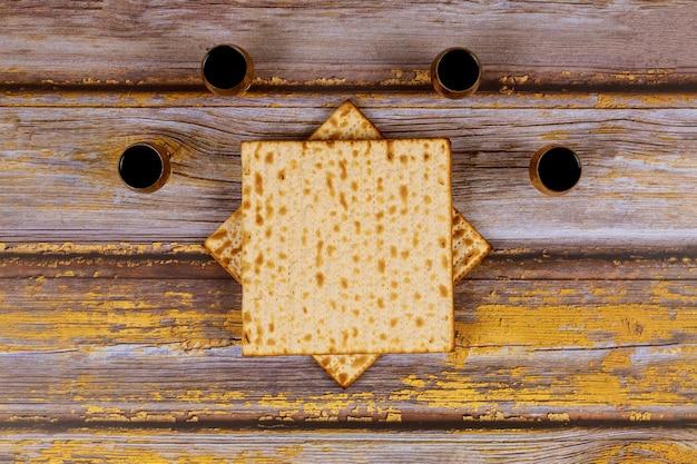 Jüdisches feiertagsbrot mit pessachwein und matzoh auf holzbrett