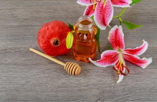 Jüdisches feiertagskonzept rosh-haschanah - jüdisches lebensmittel der granatapfelhonigosa-lilien, symbol