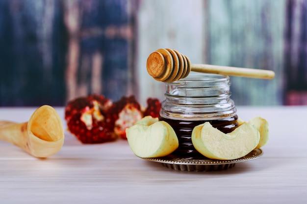 Jüdisches feiertagskonzept rosh-haschanah - shofar, torah-buch, honig, apfel und granatapfel