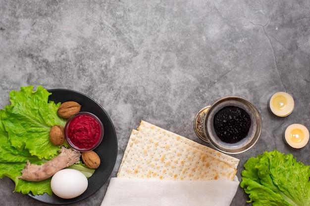 Jüdisches feiertagspessach mit wein, matze und sederplatte auf grau.