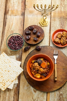 Jüdisches gericht cholent mit fleischzutaten und menora auf dem tisch