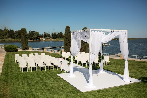 Jüdisches hupa auf der romantischen hochzeitszeremonie, heiratend im freien auf der rasenwasseransicht