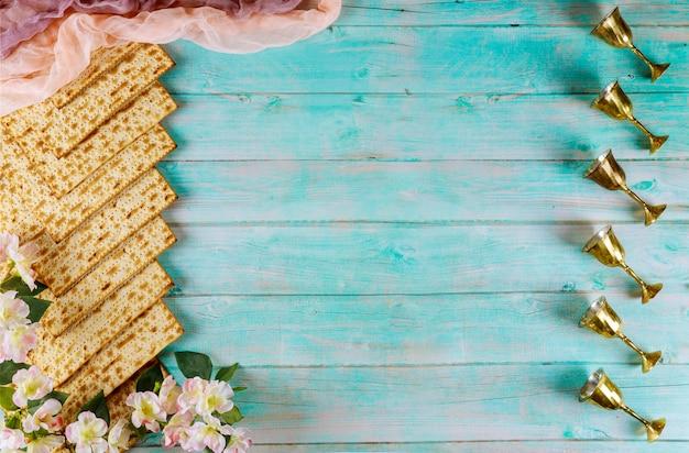 Jüdisches matzebrot auf blau mit sechs weinbechern und blumen. pessachferienkonzept