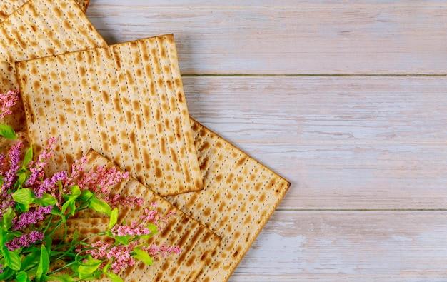 Jüdisches matzebrot mit blumen auf hölzernem rustikalem passahfestkonzept