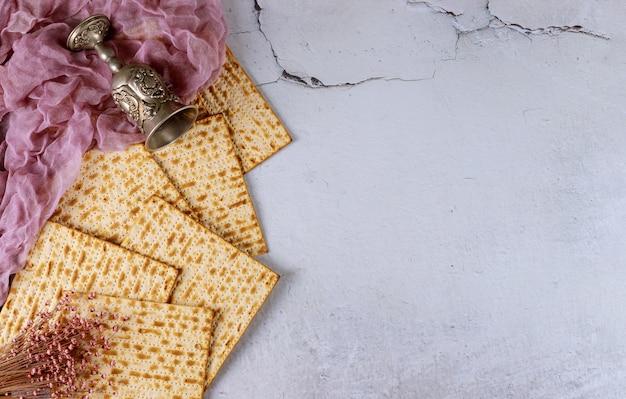 Jüdisches matzebrot mit silberbecher auf weißem pessachfeiertagskonzept