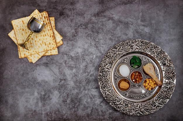 Jüdisches matzebrot mit silberner tasse und blumen auf rustikalem hölzernem hintergrund. pessachferienkonzept