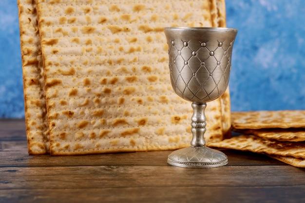 Jüdisches matzebrot mit tasse wein auf pessachfeiertagskonzept der holzoberfläche