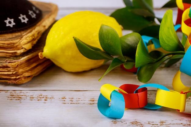 Jüdisches religiöses fest der traditionellen symbole über bunte kettengirlande des papiers von sukkot, das buchkippah betet