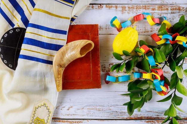 Jüdisches ritualfest von sukkot im jüdischen religiösen symbol über buntem kettengirlanden-gebetsbuch kippah tallit aus papier
