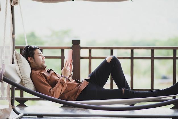 Jüngerer mann, der sich entspannt, indem er buch auf wiege liest