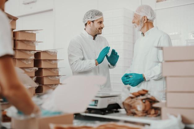 Jüngerer mitarbeiter erklärt seinem älteren kollegen, wie man packt. beide tragen weiße sterile uniformen. innenraum der nahrungspflanze.