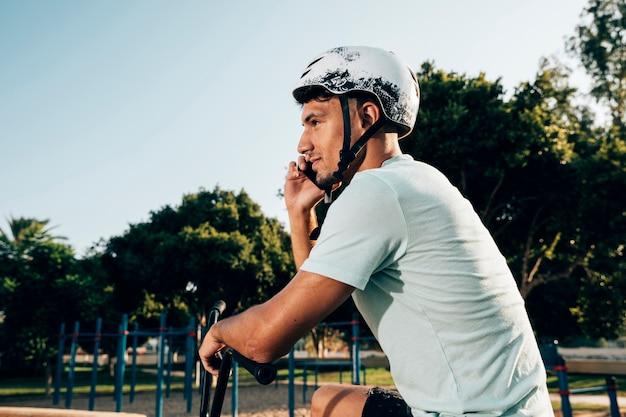 Jugend-bmx mitfahrer, der am telefon spricht