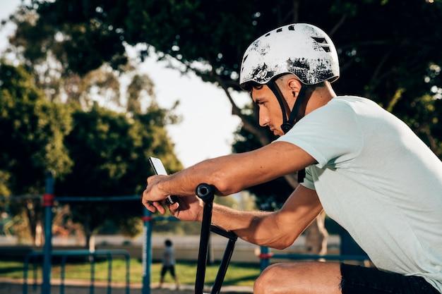 Jugend-bmx mitfahrer, der das telefon betrachtet