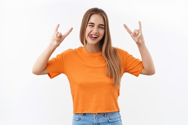 Jugend, junge leute und lifestyle-konzept. porträt eines glücklichen, sorglosen blonden kaukasischen mädchens, das spaß auf festivals oder konzerten hat, zunge und heavy-metal-, rock-n-roll-zeichen zeigt und party genießt