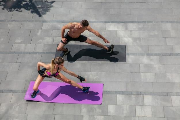 Jugend. junges paar in sport-outfit, das morgens im freien trainiert. mann und frau machen cardio- und kraftübungen und üben aktivitäten für unter- und oberkörper. sport, gesundes lebensstilkonzept.