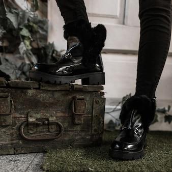 Jugend modische schwarze warme stiefel nahaufnahme. junge modische frau in den stilvollen winterschuhen mit fell steht nahe alter brust im raum
