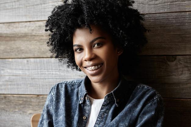 Jugend und glück. schönheit und mode. schließen sie herauf porträt der glücklichen attraktiven jungen afrikanischen frau mit zahnspangen, die ihre freizeit drinnen im modernen café genießen, gekleidet im trendigen jeanshemd