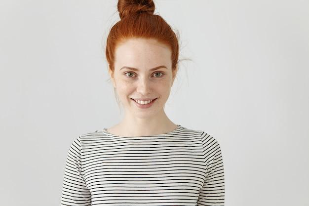 Jugend- und glückskonzept. fröhliche sorglose rothaarige teenagerin mit haarknoten und sommersprossiger, sauberer haut, die breit lächelt und sich glücklich und entspannt fühlt, während sie ihre freizeit drinnen genießt