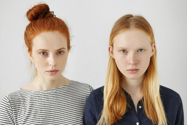 Jugend und schönheit. menschliches aussehen. menschen und emotionen. geschwister. schwestern. zwei freundinnen tragen stilvolle kleidung, posieren mit ernstem blick und denken über hausaufgaben, schulkameraden und spaziergänge nach