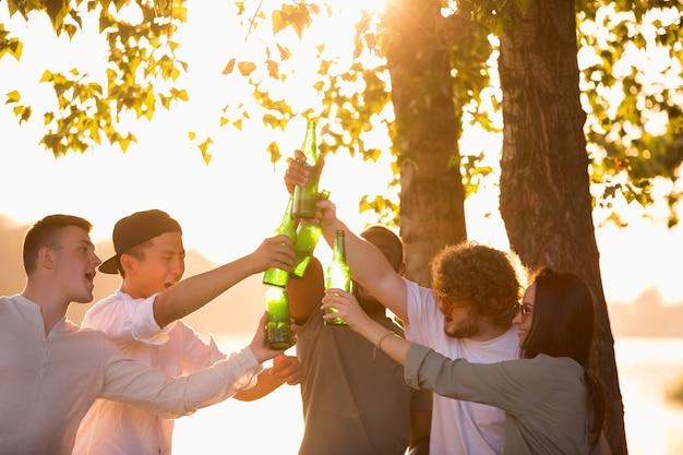Jugendgruppe von freunden, die beim picknick am strand bei sonnenschein bierflaschen klirren