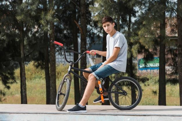 Jugendjunge, der auf fahrrad am park sitzt