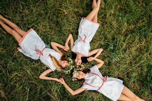 Jugendlebensstil. drei erstaunliche slawische erscheinung ethnischer volksartmädchen mit kranz von blumen, die auf gras unter baum an der natur im sommer liegen.