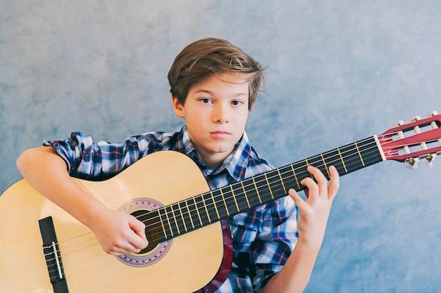 Jugendlich junge, der akustikgitarre spielt