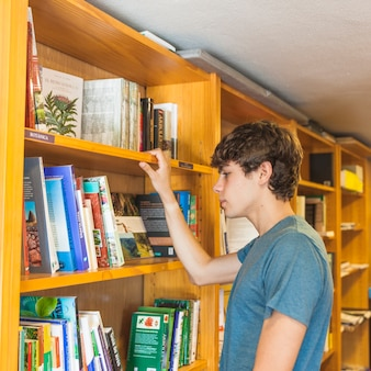 Jugendlich junge, der buch vom bücherregal wählt