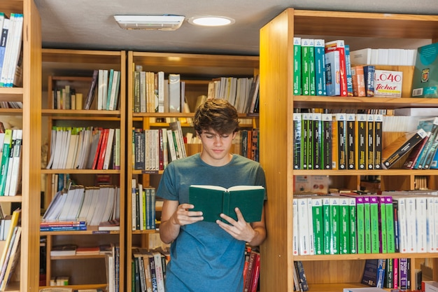 Jugendlich junge, der das lesen nahe bücherschrank genießt