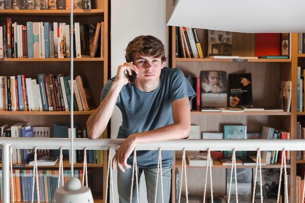 Jugendlich junge, der über smartphone in der bibliothek spricht