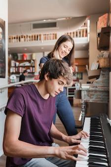 Jugendlich mädchen, das auf den freund spielt klavier hört