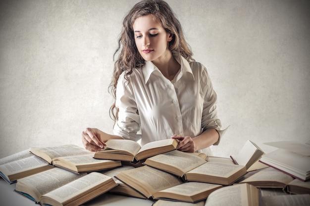 Jugendlich mädchen, das bücher studiert und liest