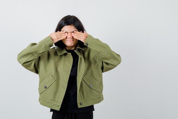 Jugendlich mädchen, das die augen mit den händen in t-shirt, grüner jacke bedeckt und unzufrieden aussieht. vorderansicht.