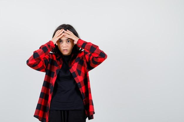 Jugendlich mädchen, das die hände auf der stirn im t-shirt, im karierten hemd hält und verwirrt, vorderansicht schaut.