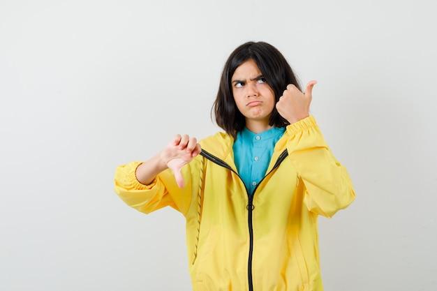 Jugendlich mädchen, das entgegengesetzte daumen zeigt, in der gelben jacke nach oben schaut und unentschlossen aussieht, vorderansicht.
