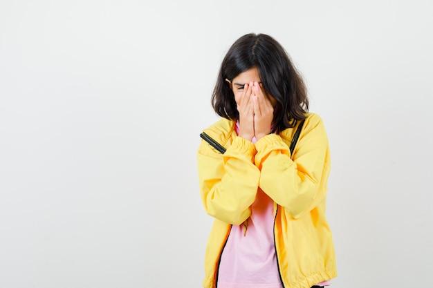 Jugendlich mädchen, das gesicht mit den händen im t-shirt, in der gelben jacke bedeckt und fokussiert, vorderansicht schaut.