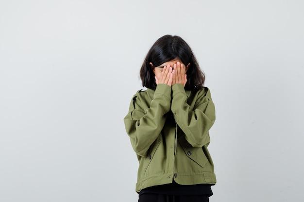 Jugendlich mädchen, das gesicht mit den händen im t-shirt, in der grünen jacke bedeckt und traurig schaut. vorderansicht.