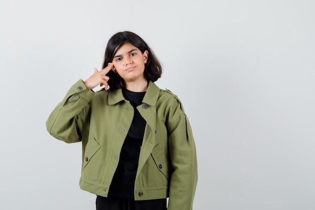 Jugendlich mädchen, das gewehrgeste im t-shirt, in der grünen jacke zeigt und selbstbewusst schaut, vorderansicht.