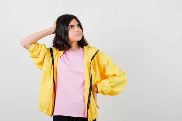 Jugendlich mädchen, das hand auf kopf und taille in gelbem trainingsanzug, t-shirt hält und wehmütig, vorderansicht schaut.